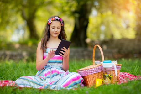girl lying down: Girl lying down on blanket and using tablet in park