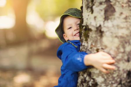 El muchacho joven que abraza un árbol