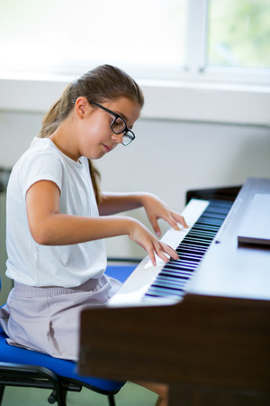 grand child: Beautiful girl playing the piano at the music school, selective focus Stock Photo