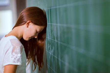 back of head: Little girl leaned her head on the blackboard