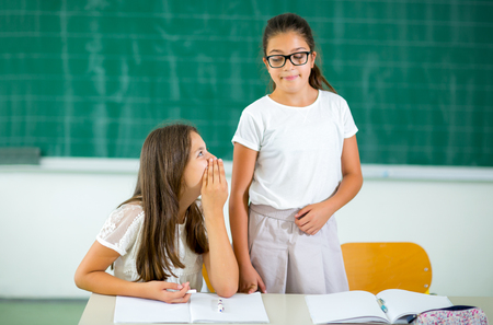 responds: One girl responds while others whispering in classroom, selective focus