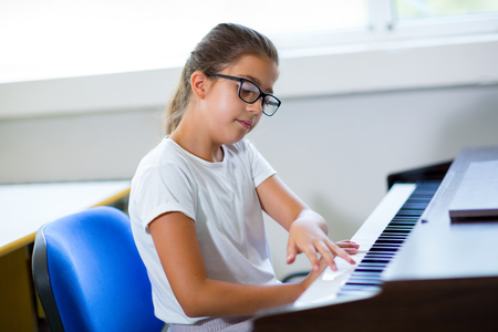 grand kid: Beautiful girl playing the piano at the music school, selective focus Stock Photo