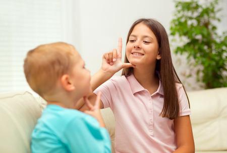 comunicar: Hermano y hermana a aprender el lenguaje de signos en el hogar Foto de archivo