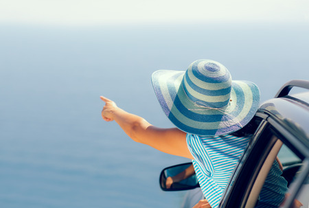 Relaxed happy woman on summer roadtrip travel vacation looking at the sea. Summer vacation concept.