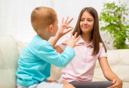 Brother and sister learn sign language at home Imagens - 60347293