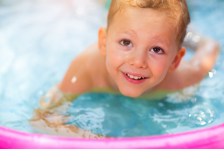 Little boy in inflatable swimming pool outdoor, having fun