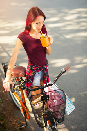 Portrait of a beautiful young girl with a bicycle in the city