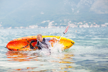 falling out: Mature man kayaking on the sea, falling out of the kayak Stock Photo