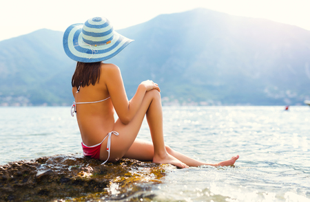 Summer vacation woman sitting on beach enjoying summer holidays looking at the sea Stock Photo