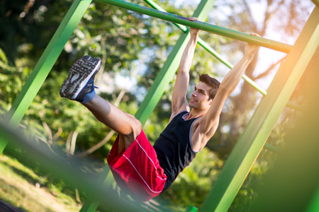 and the horizontal man: Fitness man doing stomach workouts on horizontal bar outdoors Stock Photo