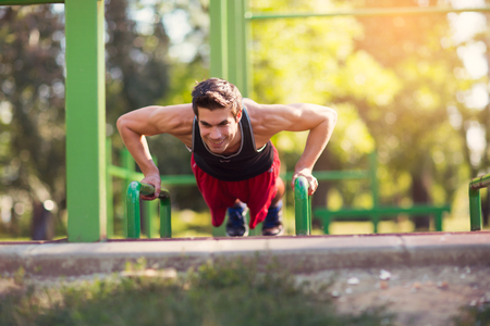 ups: Picture of a young athletic man doing push ups outdoors. Stock Photo