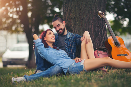 Loving couple holding each other sitting on a tree trunk on a romantic date in the park forest Banque d'images