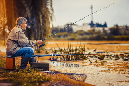 Senior man fishing on a freshwater lake sitting patiently on the shore with his rod and reel as he enjoys his retirement