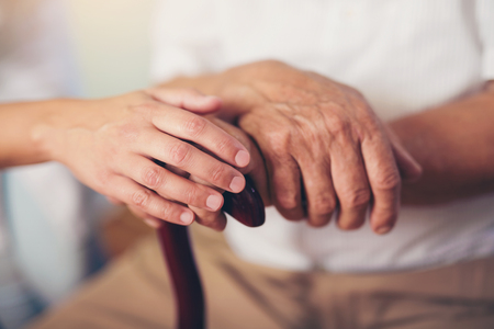 old hand: Young woman holding hand of old man with walking stick
