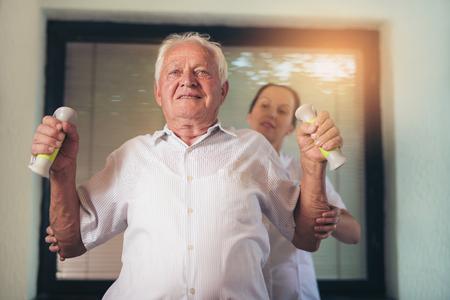 Senior man met halters in afkickkliniek met een fysiotherapeut