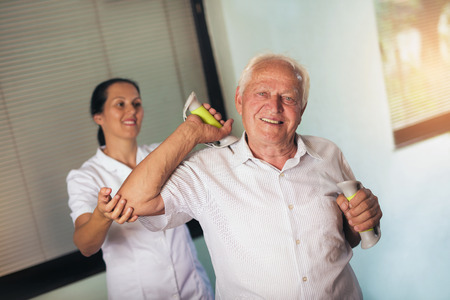remedial: Senior man with dumbbells in rehab with a physiotherapist