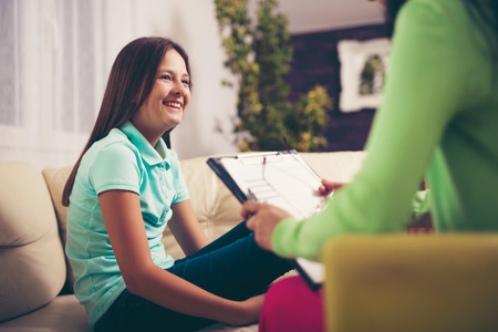 psychologists: Girl teenager is happy after a successful therapy by psychologists