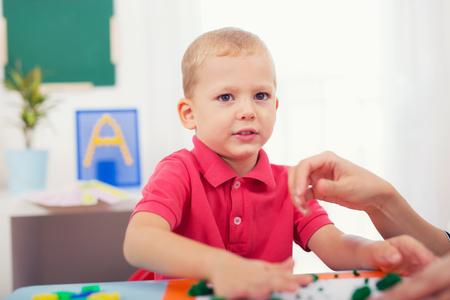 nurser: Cute little boy moulds from plasticine on table
