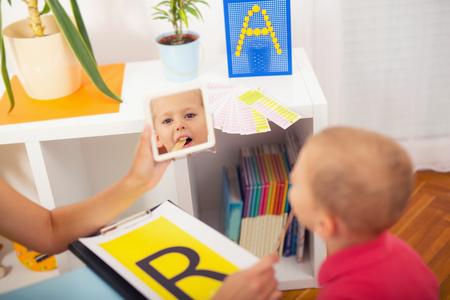 Logopädin lehrt die Jungen den Buchstaben R zu sagen Standard-Bild
