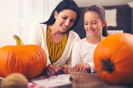Mother with daughter creating big orange pumpkin