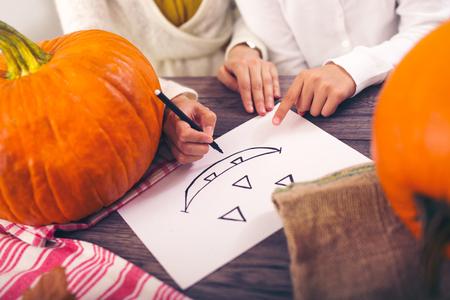 creating: Mother with daughter creating big orange pumpkin, close up drawings