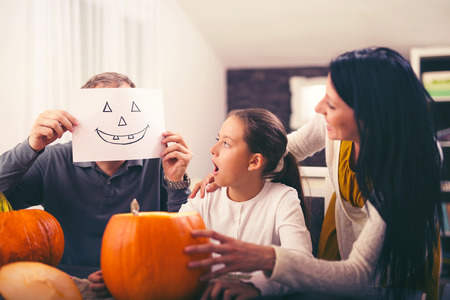 Family are celebrating Halloween. They are sitting at the table with pumpkin Stock Photo