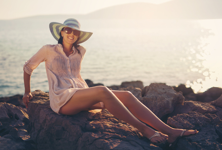 beach wrap: Woman sitting on the cape by the sea