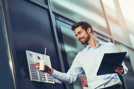 Het portret van een jonge gelukkige zakenman buiten het bureaugebouw, gaat het gebouw in