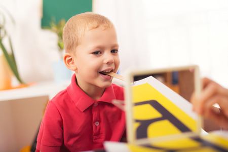 teaches: Speech therapist teaches the boys to say the letter R