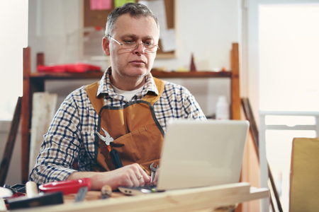 Portrait of carpenter sitting at his workshop and working with laptop Stock Photo