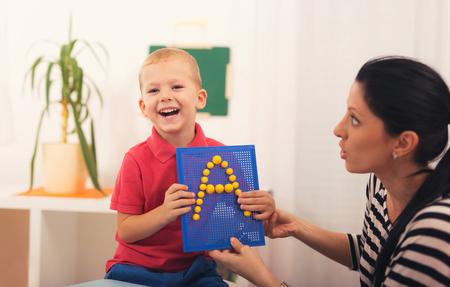 Weinig jongen tijdens les met zijn logopedist. Leren door middel van leuke en spelen Stockfoto