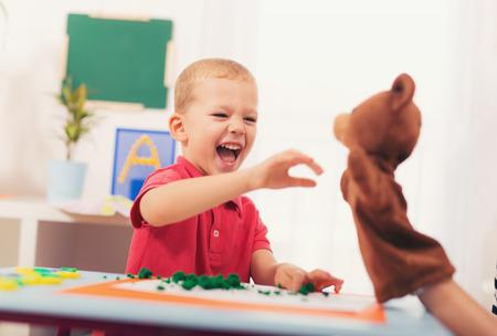 Mały chłopiec w czasie lekcji z jego logopedy. Nauka poprzez zabawę i gry