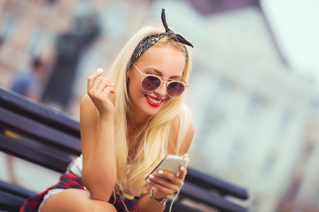 Young beautiful blonde woman using phone sitting on a bench in the street