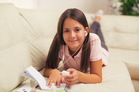 uñas pintadas: Niña con los auriculares en el hogar uñas pintadas