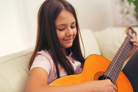 Leuk meisje beoefenen van haar gitaar lessen thuis