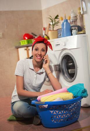 3 persons only: Woman sitting near the washing machine and talking on phone