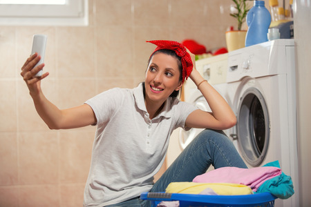 Woman sitting near the washing machine and make selfie with phone