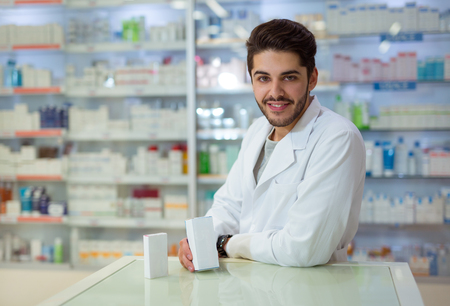 Friendly male pharmacist dispensing medicine holding a box of tablets
