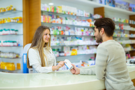 Attractive smiling pharmacist giving her client pills at the local drugstore. Stock Photo