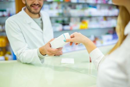 Experienced pharmacist counseling female customer in modern pharmacy Reklamní fotografie
