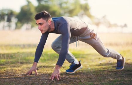concern: Handsome man exercising in forest Stock Photo