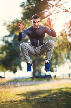Handsome man exercising in forest Stock Photo