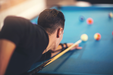 snooker halls: Handsome man playing pool in pub