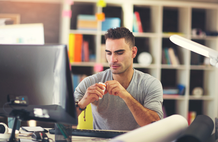 Portrait of overworked young businessman takes the medicine while sitting at workplace in front of computer. Stock Photo