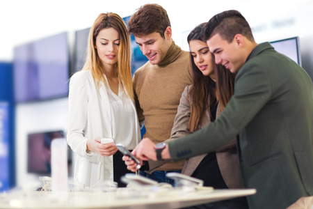 low price: Four people are choosing smart phones in store