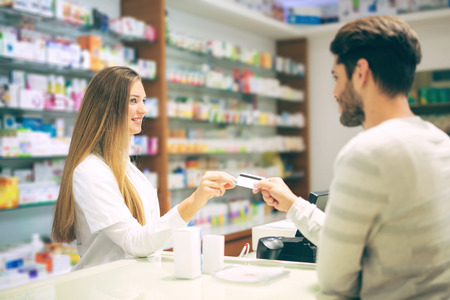 Experienced pharmacist counseling male customer in modern pharmacy and man pays with credit card