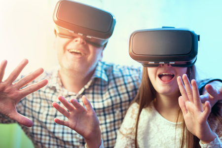 Father and daughter in virtual reality glasses having fun at home