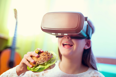 virtual reality simulator: Happy girls in virtual reality glasses eating sandwich at home