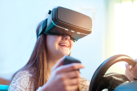 futuristic girl: Happy girls in virtual reality glasses playing video game with racing wheels  at home