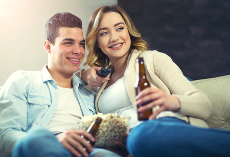 they are watching: Happy young couple sitting on the sofa at home with popcorn and beer  watching TV. They are laughing and watching a movie or television.